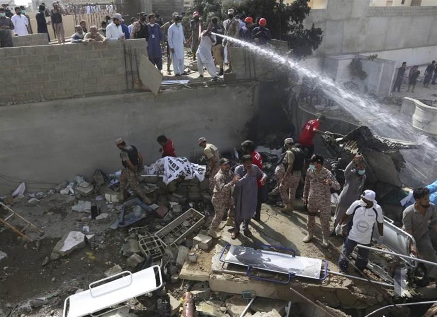 巴基斯坦國際航空(PIA)班機在喀拉蚩住宅區墜毀,志工和軍人在瓦礫堆中,挪走罹難者屍體。(美聯社)