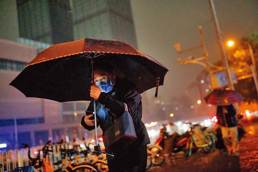 政協開幕大會散場時,一陣雷鳴暴雨,下午三點半的北京頓時被夜幕籠罩。但過沒多久,雨過天晴,陽光又重新照耀北京城。(路透)