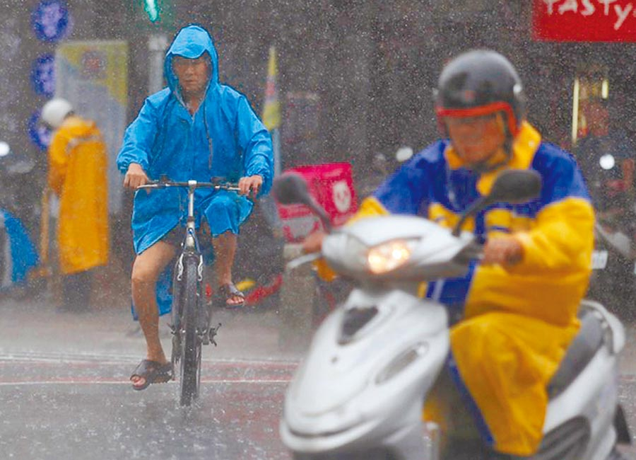 高雄街頭民眾在雨中騎腳踏車。(中央社)