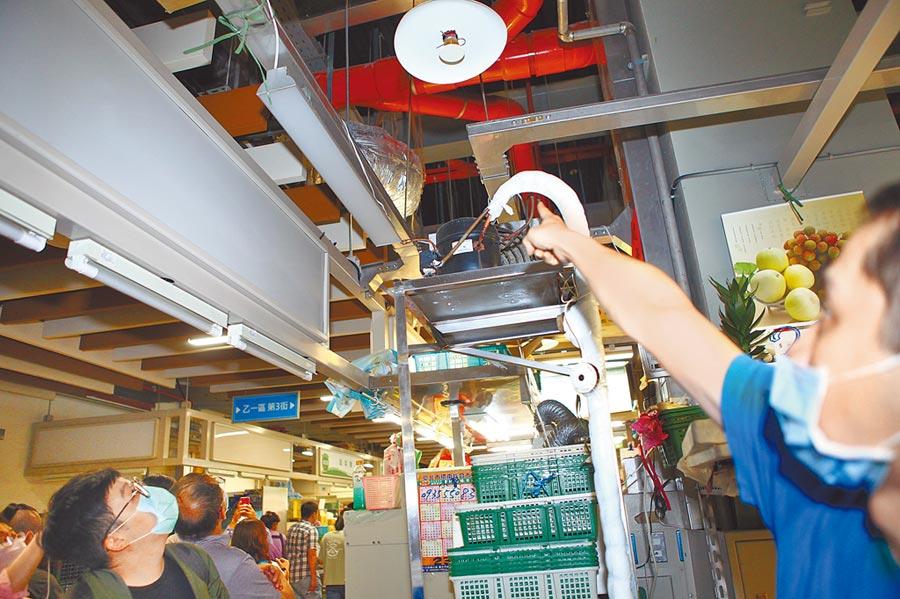 台北市議會財建委員會21日前往環南中繼市場考察,有攤商當場向議員抱怨冷氣管線、排風管不斷滴水,甚至只用膠帶隨便黏貼。(張立勳攝)