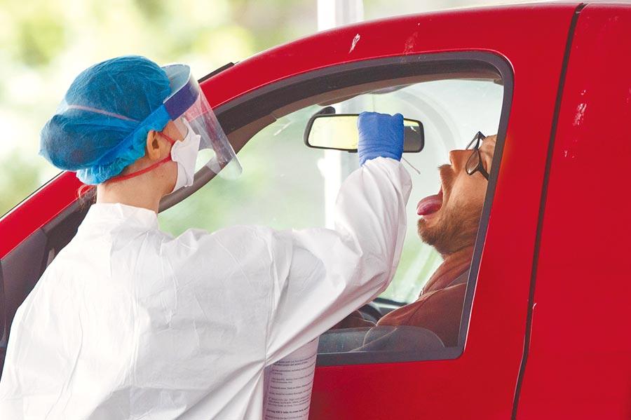 5月19日,在美國首都華盛頓,一名醫護人員對一名男子進行新冠病毒檢測採樣。(新華社)