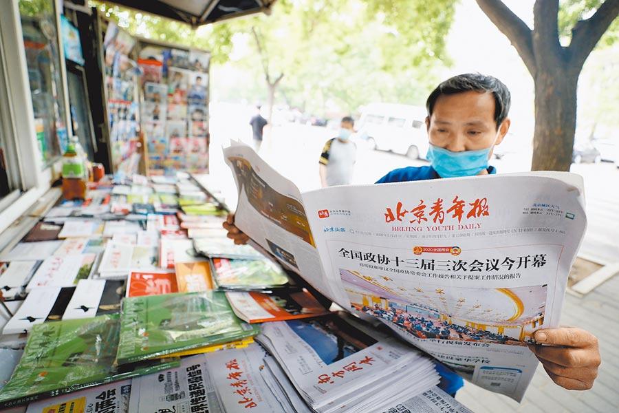 5月21日,北京朝陽區,市民翻閱刊載兩會相關新聞的報紙。(中新社)