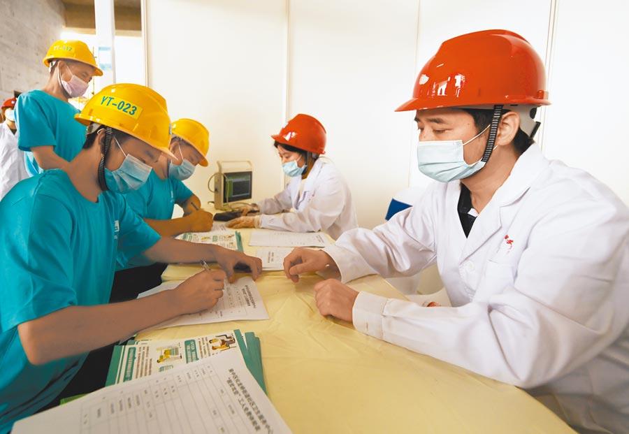 甘肅康縣農民工目填寫體檢表為上崗就業做好準備。(新華社資料照片)