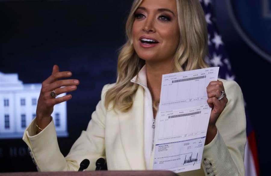 白宮新聞秘書麥肯雅妮(Kayleigh McEnany)22日在 詹姆斯布雷迪新聞簡報室(James S. Brady Press Briefing Room)召開的記者會中,秀出總統川普簽名的支票,但卻意外讓他的銀行細節曝光。(路透)