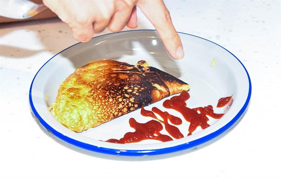 林哲熹親手製作的歐姆蛋以及番茄醬簽名。(盧禕祺攝)
