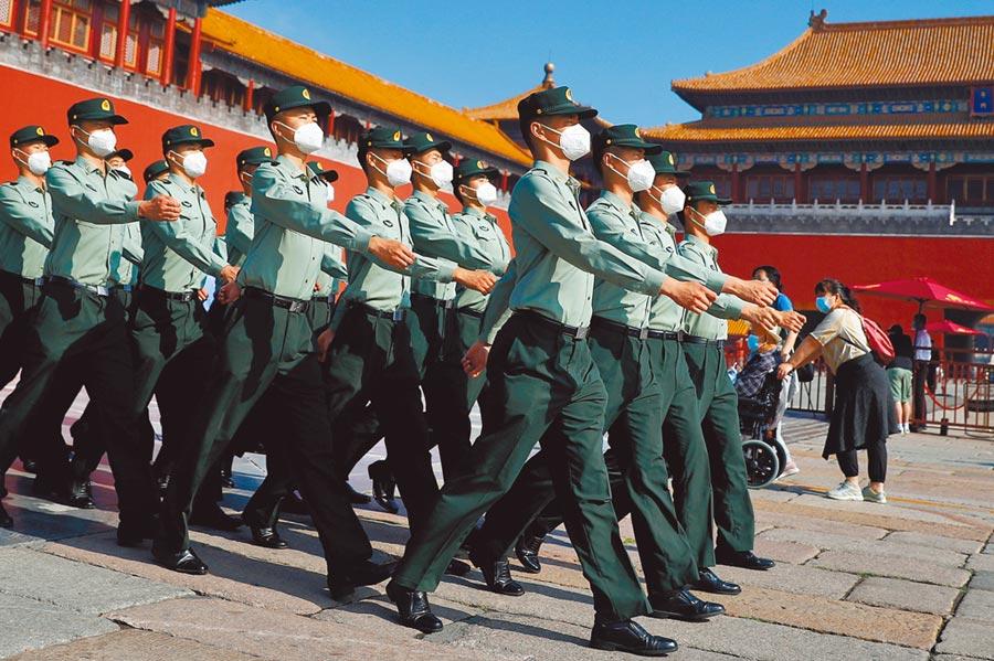 第13屆全國人民代表大會第3次會議22日在北京人民大會堂開幕,紫禁城大門前,公安警察戴著口罩列隊前進。(路透)