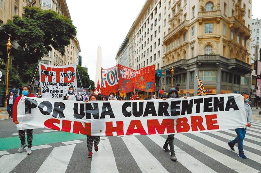 在阿根廷首都布宜諾斯艾利斯,示威群眾舉著「支持沒有飢餓的隔離」,要求當局向弱勢群體提供資源。(路透)