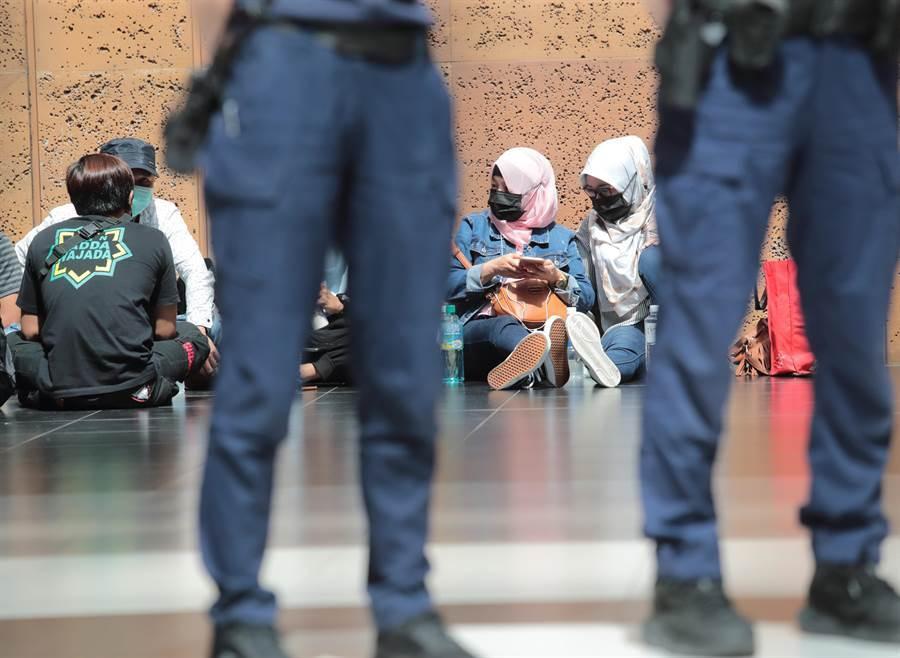 24日鐵路警察站崗勸導遵守防疫措施,移工則在管制區外保持距離席地而坐休息。(陳怡誠攝)