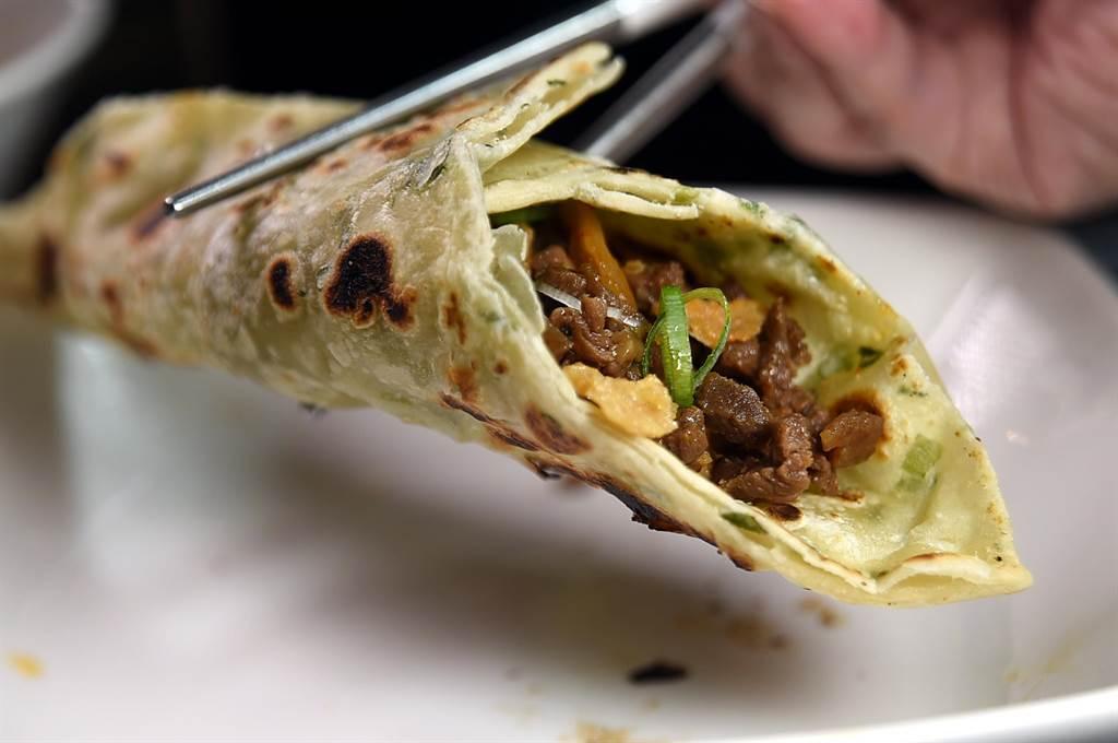 在〈翟記牛肉麵食館〉吃〈牛肉炸醬麵〉,可以用乾烙蔥油餅包捲牛肉炸醬吃食,一菜二吃很超值。(圖/姚舜)