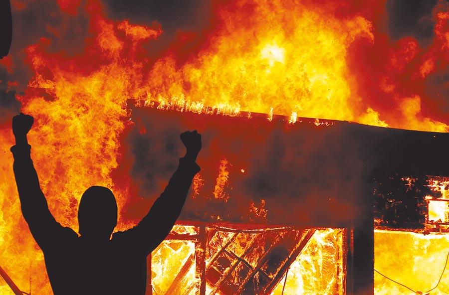 因為黑人弗洛伊德被警察暴力執法致死,大批群眾示威遊行,一名抗議者在大火前做手勢。(路透)