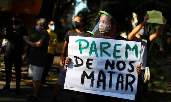31日數百人聚集在巴西里約熱內盧的州政府前,示威者手持「不要再殺害我們!」標語,抗議巴西警方此前對一名14歲黑人男孩執法過當。(路透)