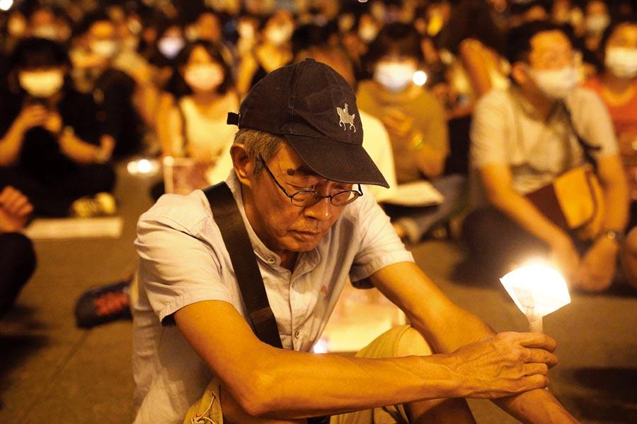 六四31週年,「遍地燭光悼六四」活動4日晚間在台北自由廣場登場,銅鑼灣書店創辦人林榮基(前)到場舉蠟燭聲援。(中央社)