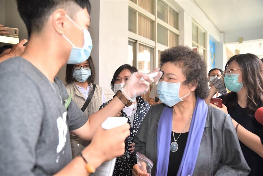總統府前祕書長陳菊(右)6日上午前左營區新上國小的投開票所投票,工作人員幫她量額溫。(林瑞益)