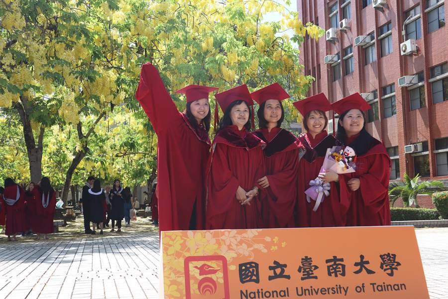 國立台南大學畢典今日(7)登場,雖受疫情影響,規範較往年多,但仍不減畢業生喜悅,與校園內的阿勃勒合影。(李宜杰攝)