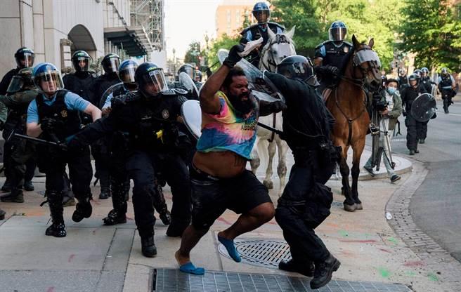 鎮暴警察1日設法驅散白宮對街拉法葉公園(Lafayette Park)抗議者的畫面。(路透)