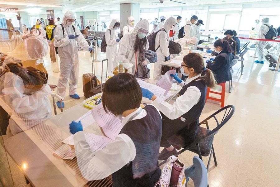 香港大學醫學專家建議,香港地狹人稠難以防範人群感染,最重要是將每日檢測數目提升至7000人。圖為波蘭航空首班包機7日抵台,由檢疫官逐一審核旅客提出的健康聲明暨集中檢疫通知書內容。(陳麒全攝)