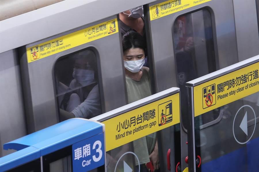 北捷上班尖峰時段湧進大批乘客,民眾幾乎人人都戴上口罩。(黃世麒攝)