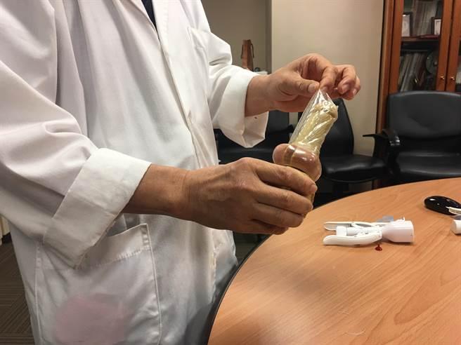 包皮過長是包皮炎的成因之一,圖為書田診所泌尿科主任殷約翰以保險套示範包皮過長的問題。(林周義攝)