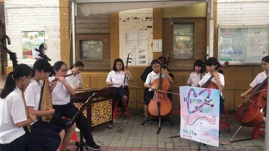 嘉義市民生國中絲竹團及打擊團今天到嘉義火車站前快閃表演,帶給大家好心情。(民生國中提供)