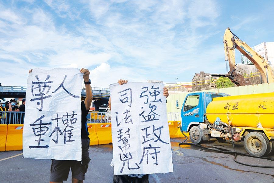 張宅遭拆後,自救會成員趕抵現場,拿出抗議布條,指控「強盜政府、司法幫凶」。(李宜杰攝)