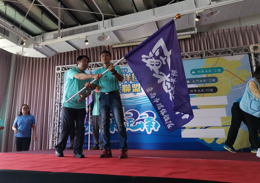 環保局13日舉行年世界海洋日「護海大聯盟」授旗儀式,由黃偉哲親自授旗給台南市7處漁港環保艦隊代表。(劉秀芬攝)