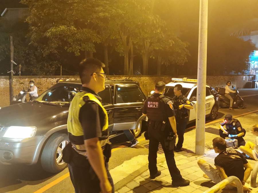毒鴛鴦當街衝撞警車,遭警方逮捕後上銬坐在地上,模樣狼狽。(讀者提供/程炳璋台南傳真)