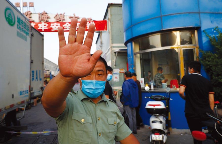 北京再度發現境內新冠肺炎確診者,由於部分患者曾到過傳統市場,因此官方已下令關閉市內多個批發市場。圖為位於北京豐台區的京深海鮮市場12日已封鎖,戴著口罩的保安禁止外人進入。(路透)