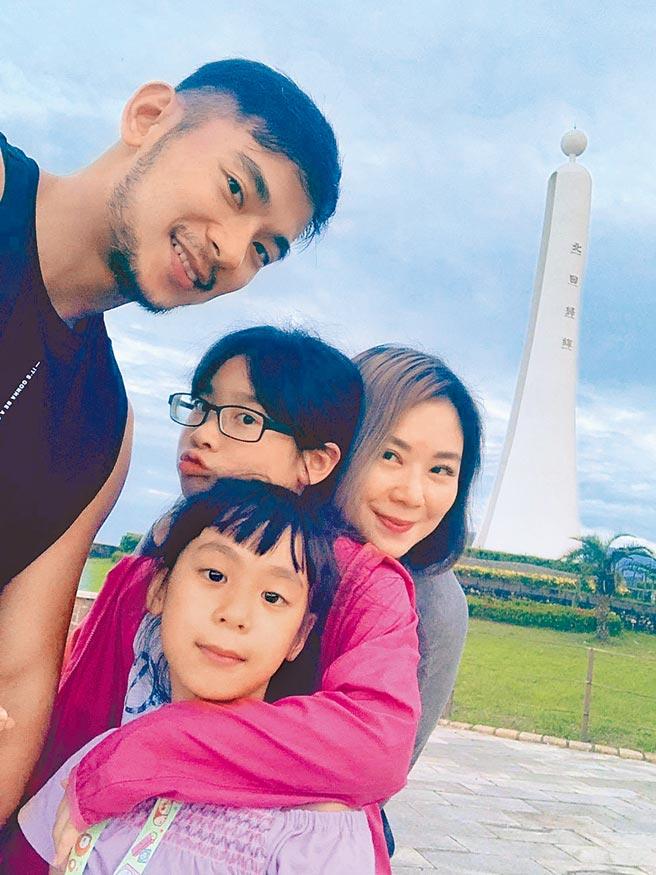 亮哲(左)與老婆黃毓棠(右)及兩個女兒開心在台東「北回歸線」前合影。(亮哲提供)