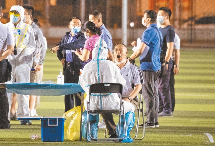 北京市民13日晚在宣武體育場進行核酸採樣。13、14日2天共確診44例。(中新社)