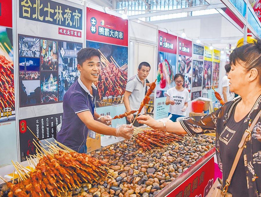 民眾在天津.台灣商品博覽會上品嘗台灣小吃。(新華社資料照片)