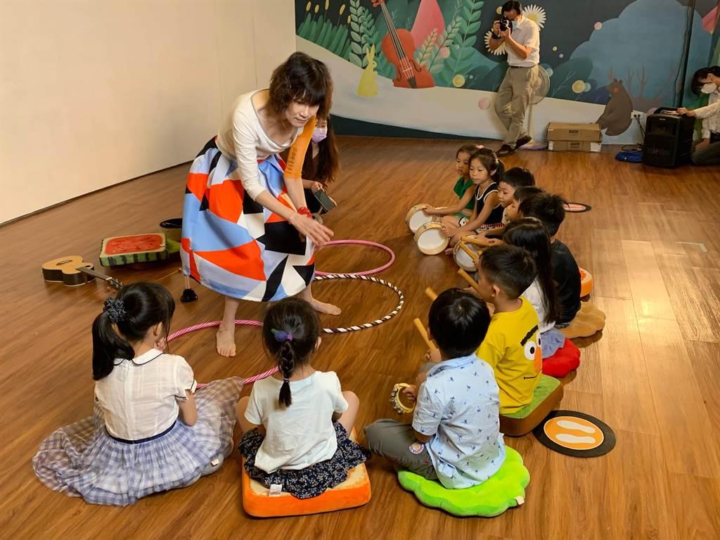 朝陽科大人文暨社會學院院長李玲玉(左)化身為說故事姊姊,拿起《出發吧,魔法森林音樂會!》繪本帶領孩子們唱唱跳跳。(林欣儀攝)
