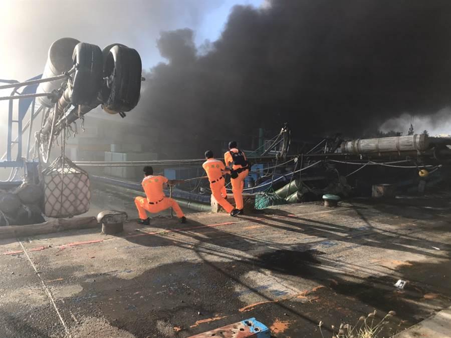 由於火勢遭受風勢助長,陸續延燒到隔鄰漁船,海巡隊員想盡辦法搶救。(戴志揚翻攝)