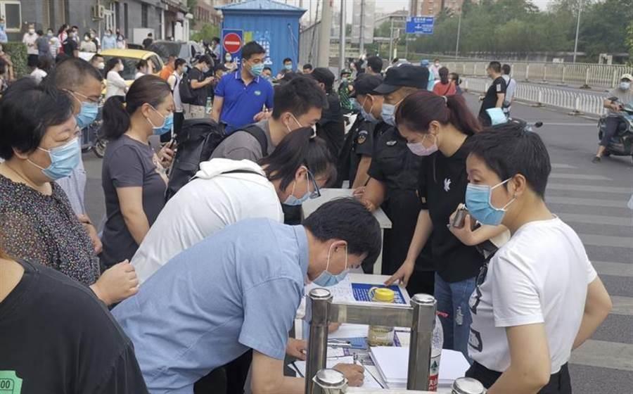 北京社區工作人員16日登記進出人員信息的畫面。(中新社)