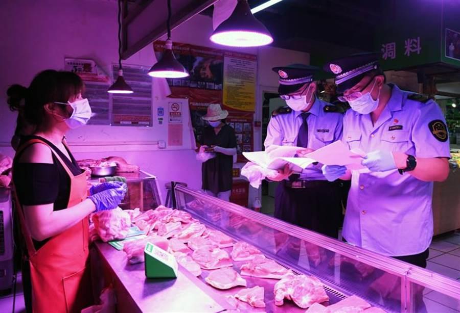 北京恐正面臨第二波疫情來襲,對此陸疾病預防控制中心主任高福16日表示,北京市最新的新冠疫情可能不是5月底、6月初才出現的,時間可能要往前推一個月。圖為北京市海澱區的增光鴻運市場,執法人員對商戶所售鮮肉的進貨渠道進行檢查。(新華社)