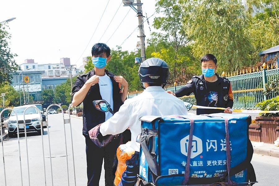 北京許多社區再次升高戒備,進行封閉式管理,進出社區人員都要詳加盤查。(路透)