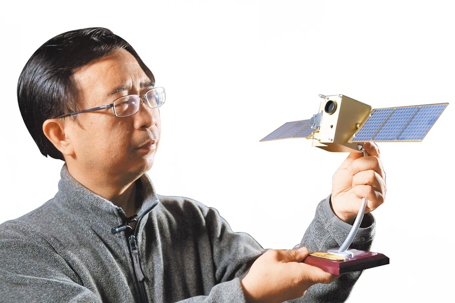 大陸科學家潘建偉與「墨子號」量子衛星模型。(新華社資料照片)