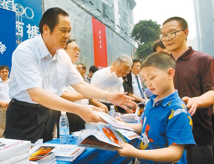 2004年6月26,時任重慶市公安局長朱明國(左一),在街頭向青少年及家長發放禁毒宣傳資料。(新華社資料照片)