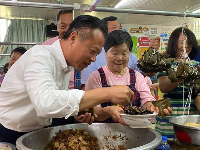 82歲的吳秋艷傳授縣長翁章梁包粽子的「撇步」。(張亦惠攝)