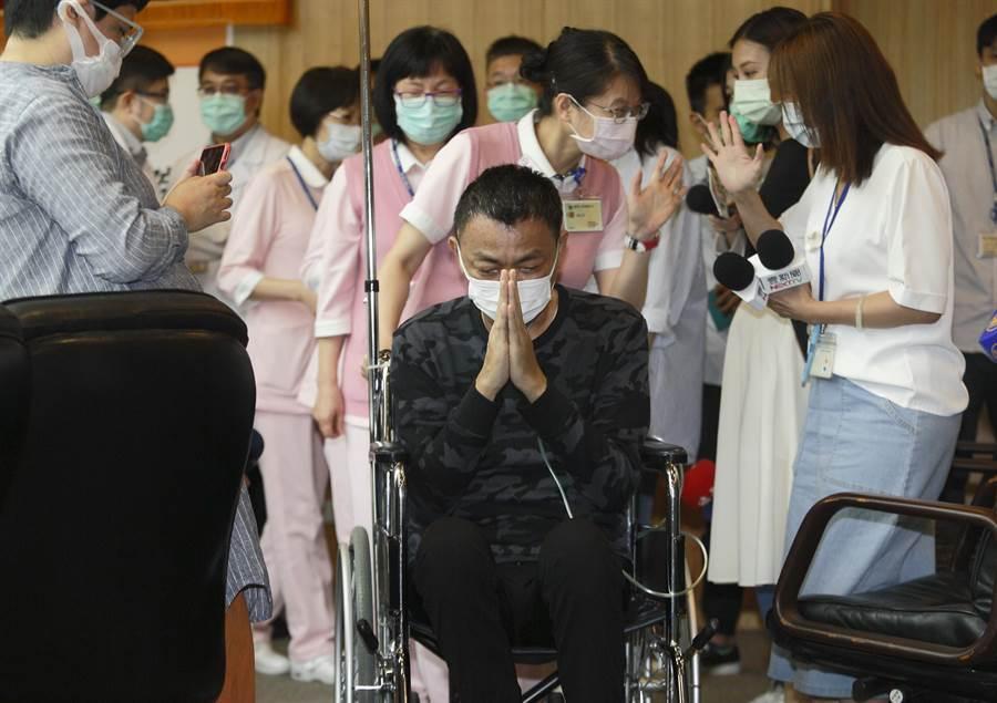 台灣目前445例新冠肺炎確診個案中有17例在台大醫院治療,台大18日邀請一度陷入重症、使用葉克膜天數為全台最久的A先生(中)舉行康復記者會,分享治療心路歷程,由於台大醫師不僅跨科別協力治療,也與護理師組成照護小組協助拍痰,讓A先生一開口就數度感謝醫護人員,讓他沒踏進鬼門關,記者會結束時雙手合十,滿心感激。(張鎧乙攝)