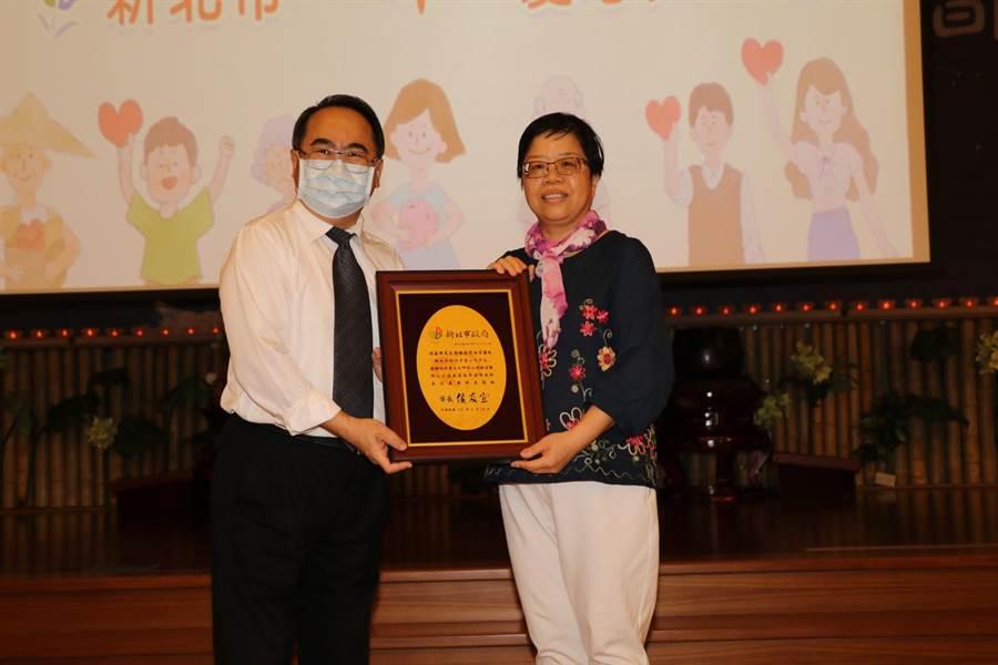 新北市社會局副局長林昭文致贈感謝牌給游惠玲。(新北市社會局提供)