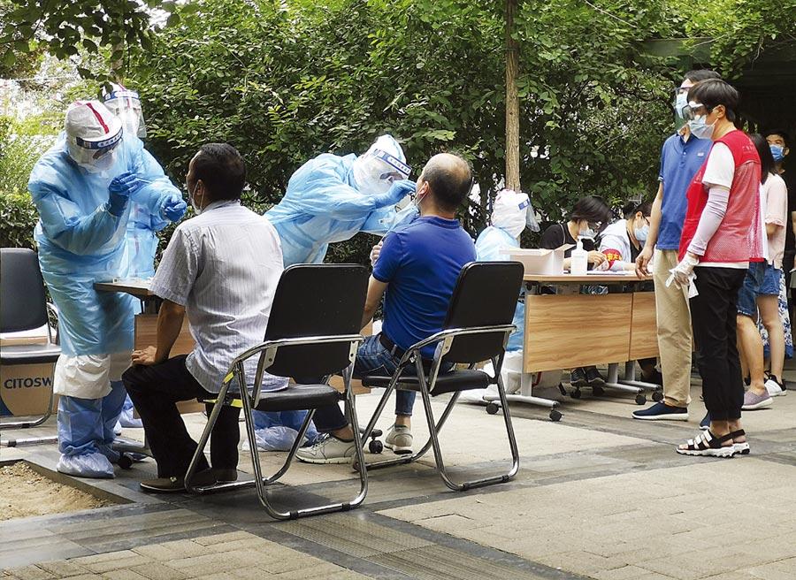 北京疫情防控升級,離京要持7日內核酸檢測陰性證明。圖為北京工作人員為社區居民進行核酸檢測。(中新社)