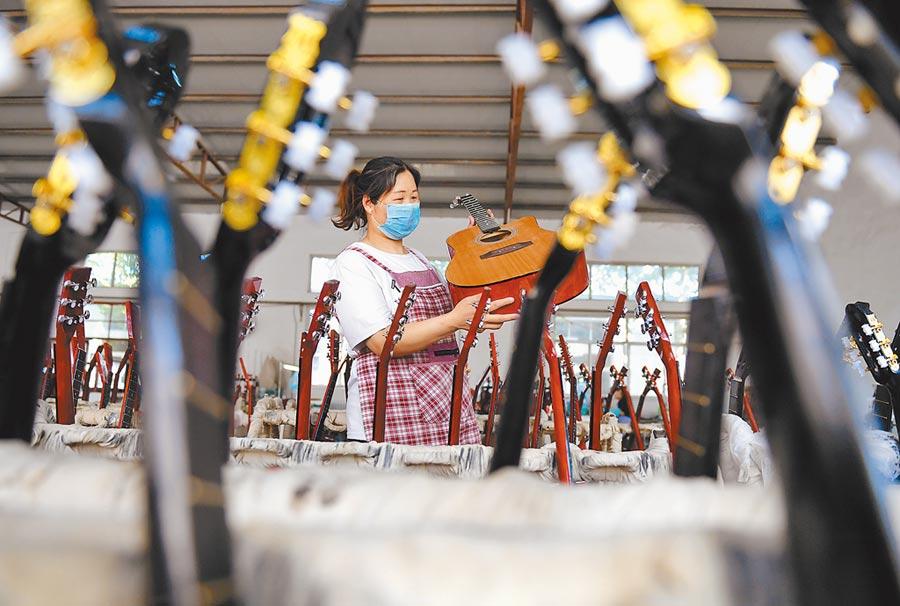 6月2日,河北武強縣一家樂器廠生產線,員工在檢查吉他。(新華社)