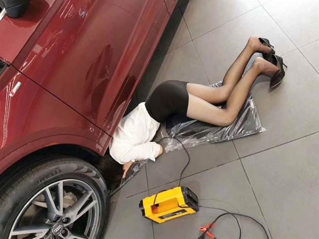 网友在脸书社团贴出一张照片,一位身穿套装的汽车女业务埋首在轿车底部翻找,身穿的白衬衫和黑丝袜成强烈对比。(摘自爆废公社)