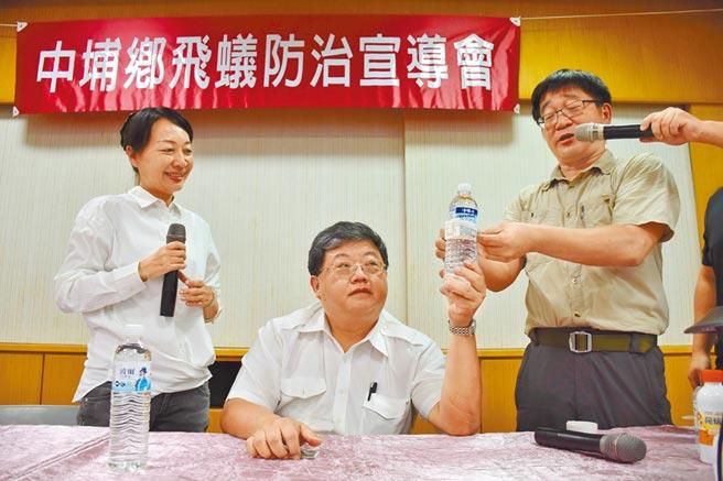 國立彰化師範大學生物系教授林宗岐(右)與嘉義縣中埔鄉長李碧菁(左)一起示範如何放置餌劑。(呂妍庭攝)