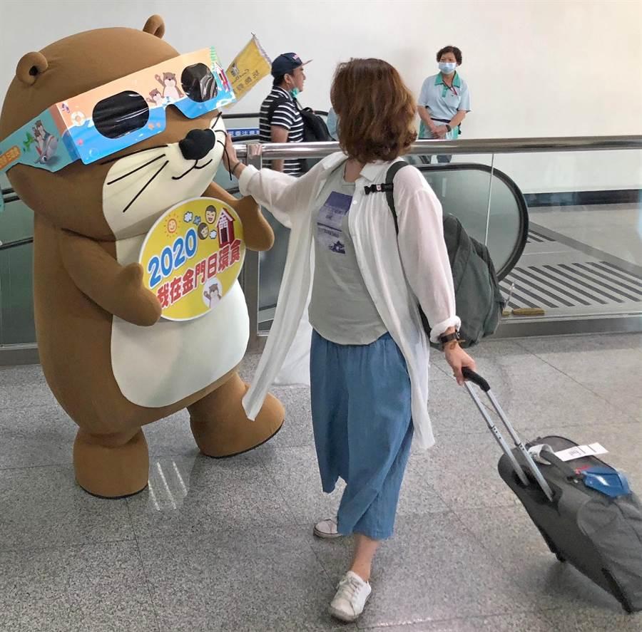 金門觀光小天使水獺「阿特」在尚義機場,與跨海觀賞日環食的遊客親切互動。(李金生攝)