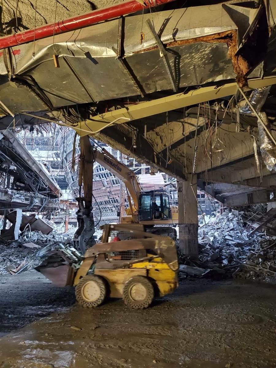 現場疑似8樓樓板坍塌,約100平方公尺的石塊墜落到1樓,砸到1樓的一輛小山貓及小貨車,消防人員到場開挖搜救。(民眾提供/林郁平台北傳真)