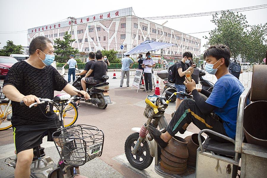 戴著口罩的北京市民,路過已關閉的新發地市場。(美聯社)