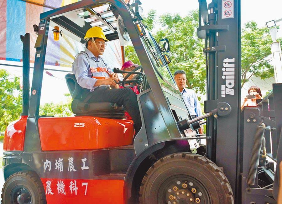 屏東縣勞動大學19日開學,其中有堆高機課程,縣長潘孟安也學習如何操作。(潘建志攝)