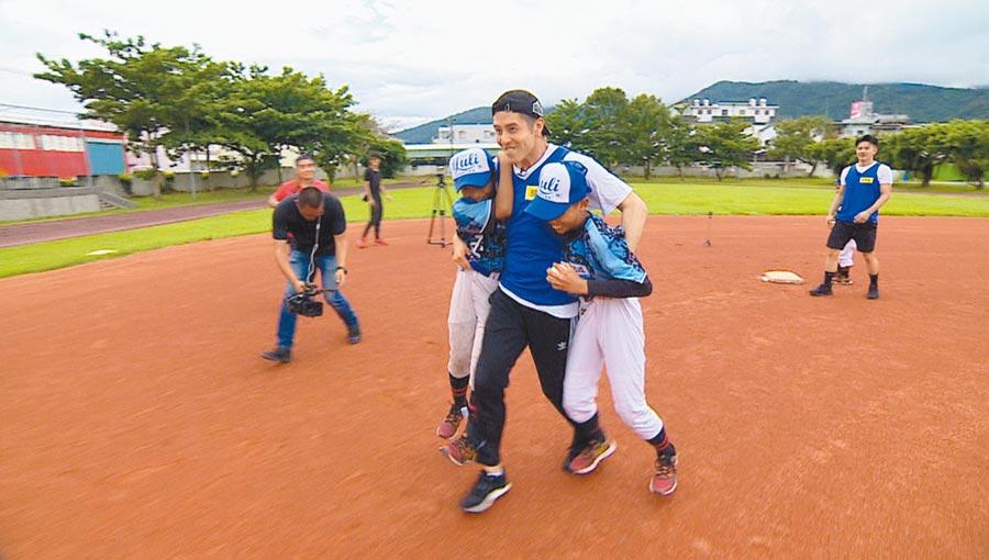 胡宇威(中)扛起2個小棒球員,表情逗趣。(華視提供)