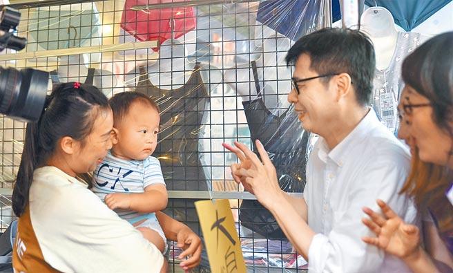 投入高雄市長補選的前行政院副院長陳其邁(右),20日上午到岡山區文賢市場掃街時逗小朋友玩。(林瑞益攝)